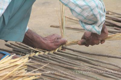 Tharu villager weaving a basket