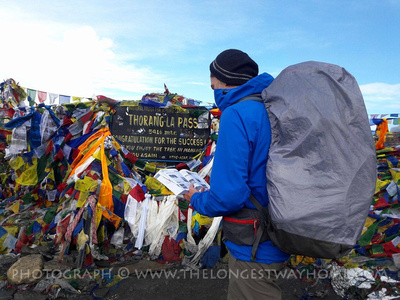 A trekker reading from The Longest Way Home Guidebook to Nepal at the Throng La Pass