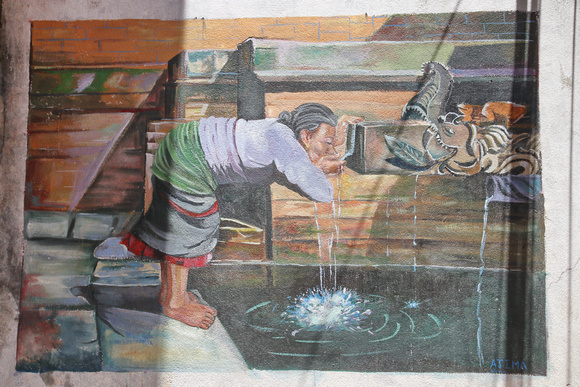 Street art of a lady drinking from a hiti in Kathmandu