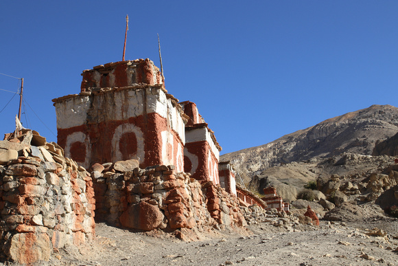 Colorful chorten and wall line the road to Tetang
