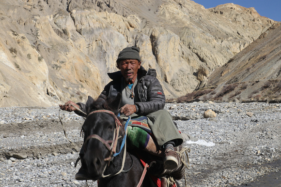 Horseman riding through a valley in Upper Mustang