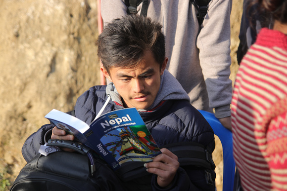 School boy reads a guidebook