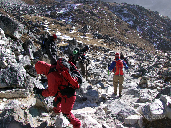 Trekkers climbing over boulders on the Everst Base Camp Trek