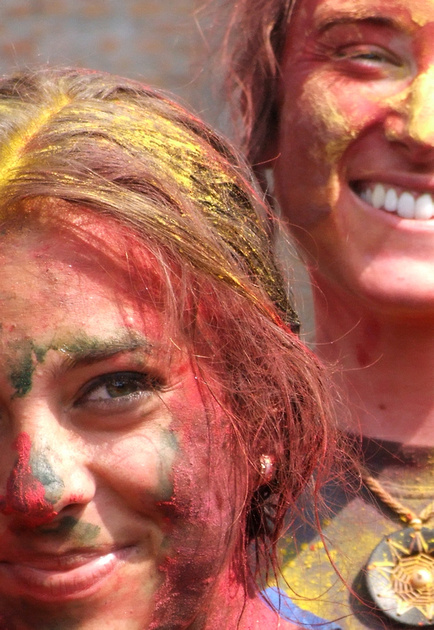 Girls smiling and covered in colored dye during the holi festival in Nepal
