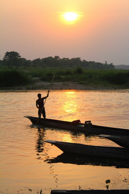 Boatman comes in during sunset on the rapti river in Chitwan