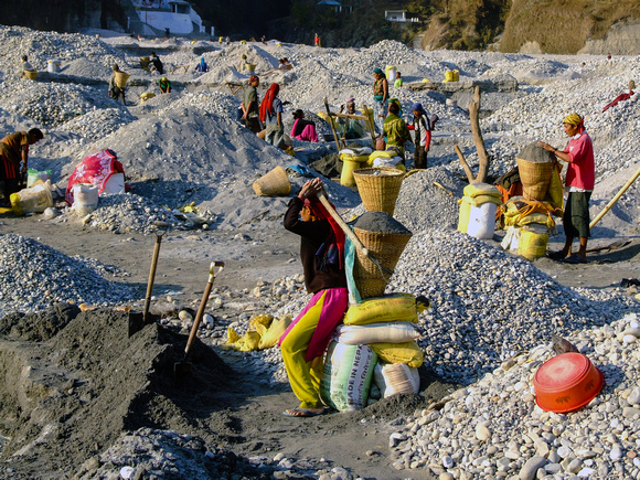 Young woman gets ready to carry a heavy basket of rubble from the Seti River Mine