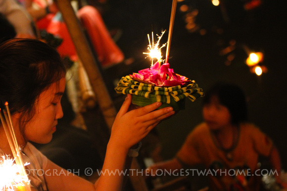 Praying woman at Loi Krathong with a girl in the water behind