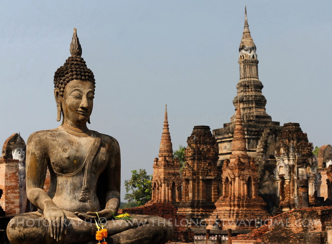 A Buddha statue with Wat Mahathat in the background in Sukhothai, Thailand
