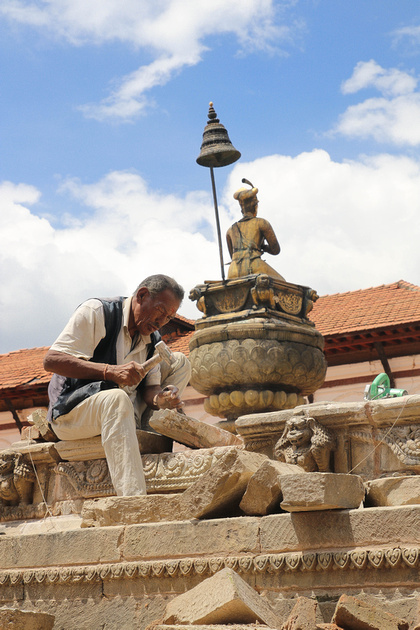 Stonemason working beside King Pratap Malla column in Bhaktapur