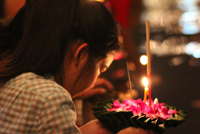 Thai girl praying with a Loi Krathong