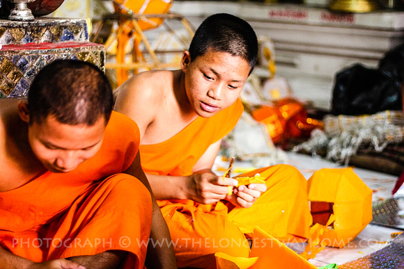 Monk looking on as a new monk learns how to cut a decoration of this paper lantern