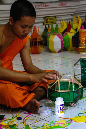 Monk adding translucent paper to a lantern