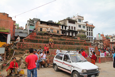 Taxis park in the historic durbar square while people sit among the bricks around the collapsed Trailokyan Mohan Temple