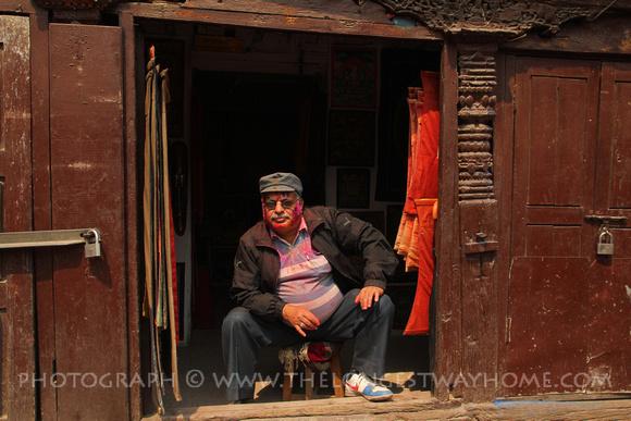 Man in a shop enjoying Holi