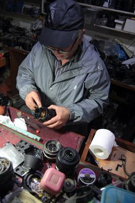 Kiran working a lens at the Camera Repair Store