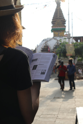 Tourist reading Nepal Guidebook