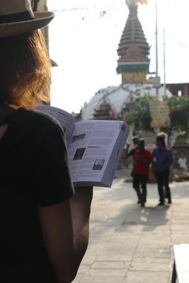 Tourist reading Nepal Guidebook