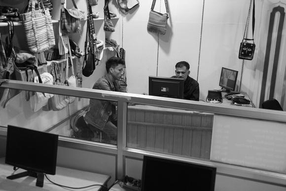 Ashok sits behind his desk in Kunil Cyber (Narshing Chowk) looking at his accounts