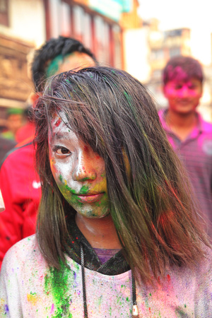 Girl in silver and color paint during Holi