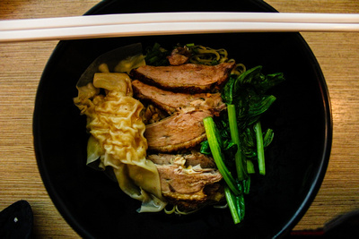 A bowl of roasted duck with chopsticks