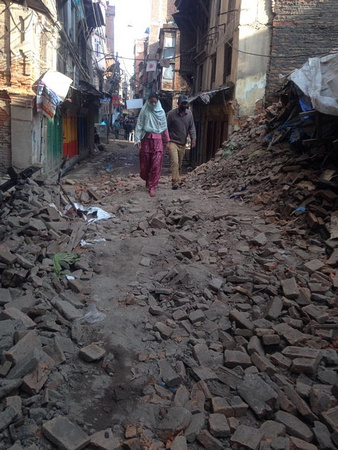 two people walk alone down a road in Kathmandu after the earthquake
