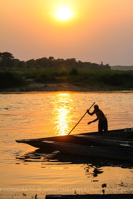 Boat and boatman during sunset in Chitwan National Park