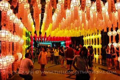 People posing under colored lanterns