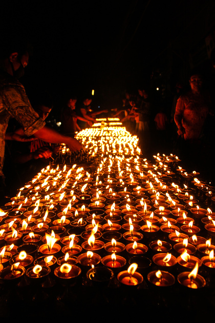 Lighting candles at night in Boudhanath
