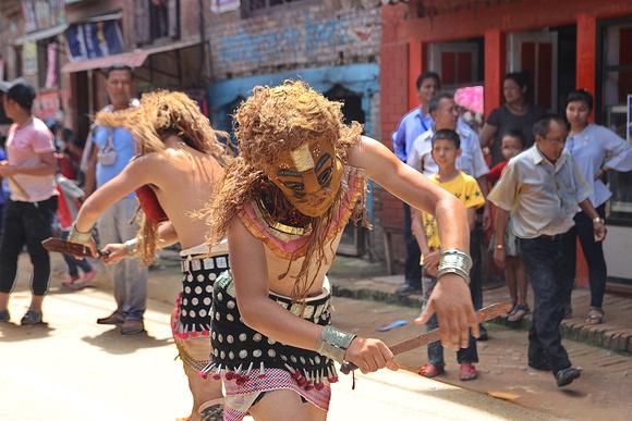 Two men displaying dance skills during Gai Jatra