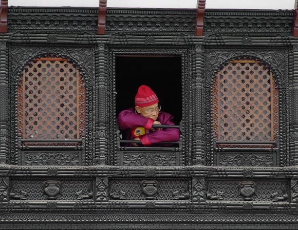 Old monk leaning out a window in Kathmandu, Nepal
