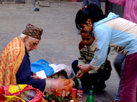 Children get a blessing before going to school in Kathmandu