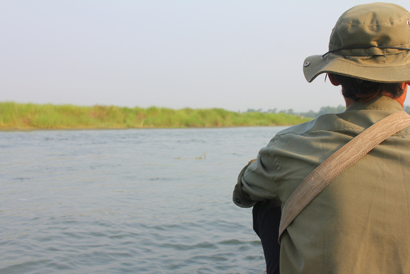 Guide on a paddle boat going down the Rapti river in Chitwan