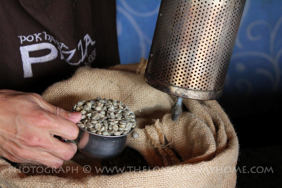 Loading fresh green coffee beans into the inner roaster