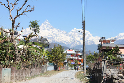 Road beside budget hotels in Pokhara with mountain views