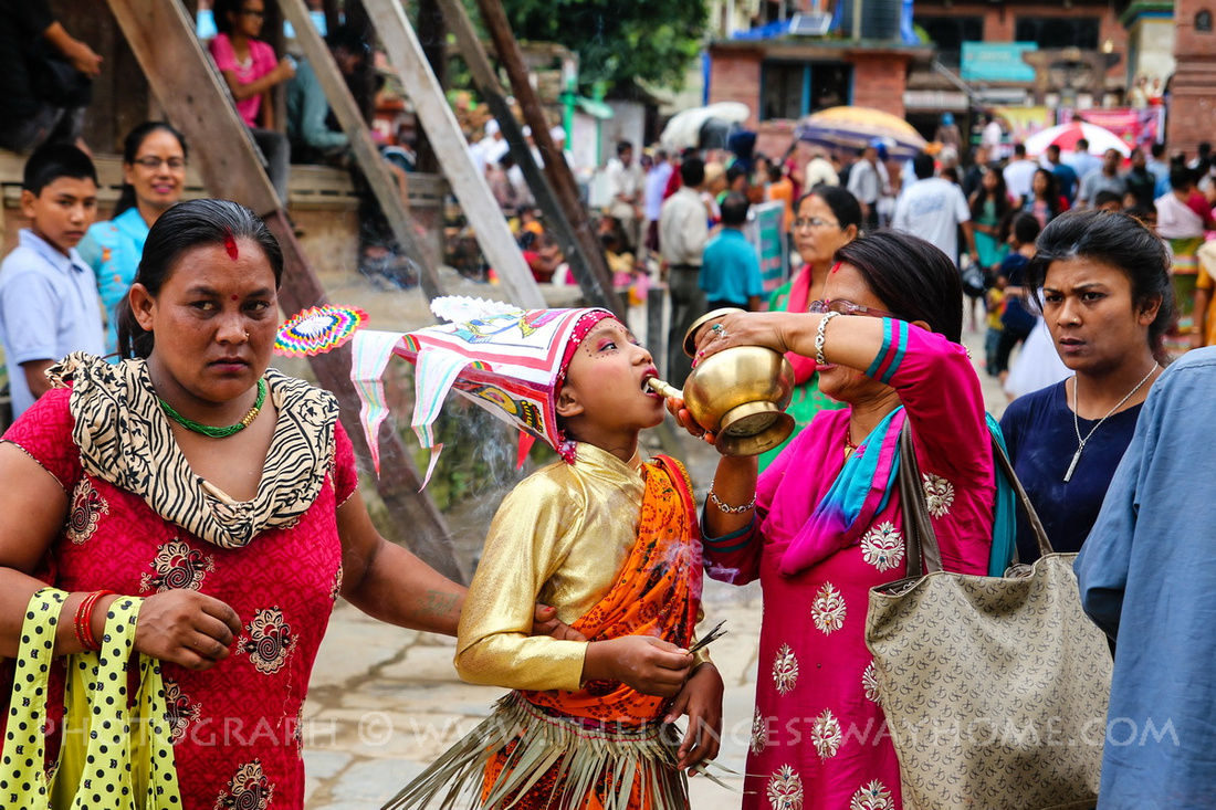 Girl is given milk during Gai Jatra in Nepal
