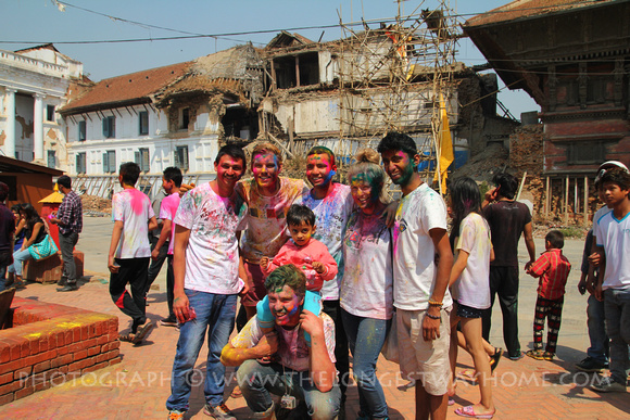 Tourists during Holi with earthquake damage behind them