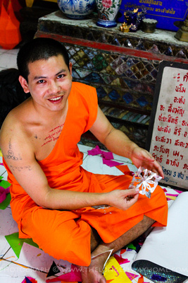 A skilled monk shows his work off in making decorations