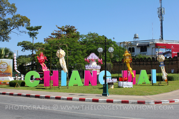 Colorful decorations around sign for Chiang Mai