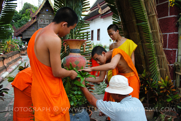 Monks and teacher prepare flowers for Yee Peng