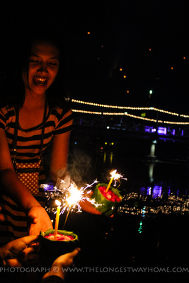 Girl lighting sparklers during Loi Krathong