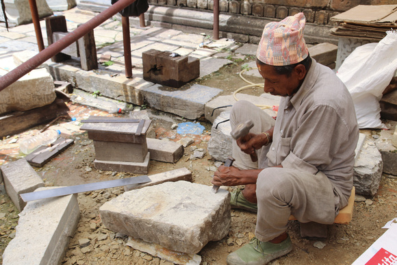 A stone mason works on the Krishna Mandir building at the center of Patan