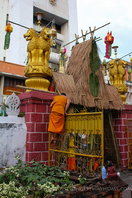 Monk climbing up a gate to install wiring for the lanterns at Yee Peng