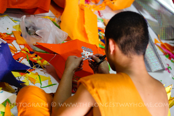 Monk cutting tinsel to decorate a paper lantern