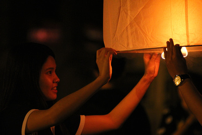 Girl Lighting Lantern at Yi Peng