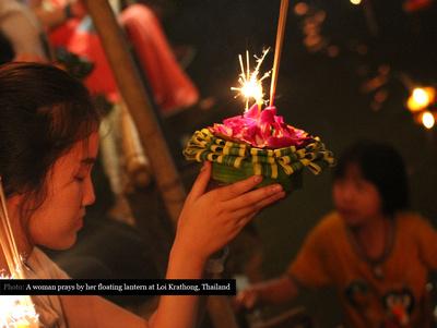 Woman praying with floating lantern during Loi Krathong