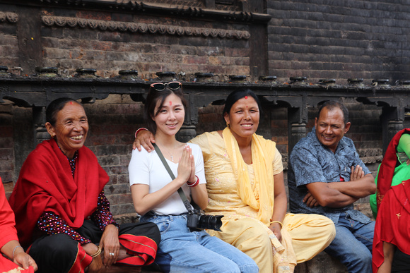 A tourist posing for photos during Bhaktapur's Gai Jatra Festival