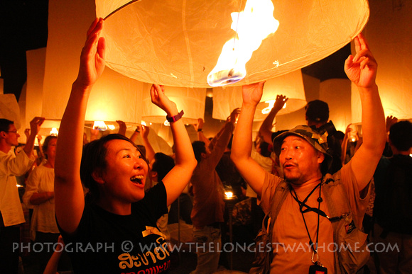 Two people releasing a sky lantern at Yee Peng