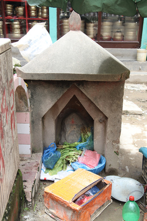 A Ganesh and unknown shrine beside it being used to prop up vegetables in Kathmandu