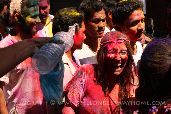 Girl getting covered in color and water during Holi