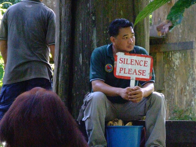 "Man holding ""silence please"" sign in Sepilok"